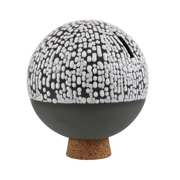 The Orb is a hand-cast porcelain money bank glazed in a myriad of hi-fire color combinations. It is available in white and grey porcelain. Each Orb rests on a c