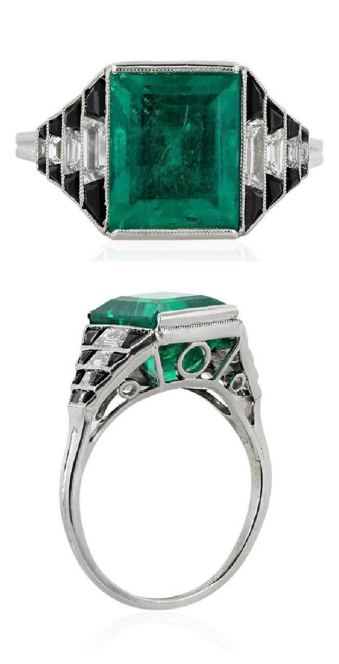 An Art Deco platinum, diamond, Columbian emerald and onyx ring. Set to the centre with a Columbian emerald weighing 4.36 carats, flanked by step cut trapezoid diamond and custom cut onyx and a filigree under-gallery.