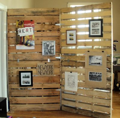 Pallets as room dividers and supports for framed photos.