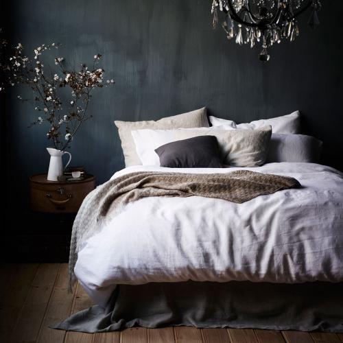 darker walls, simple bed, white linen.