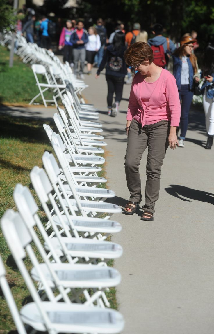 "Ann Laws, a staff member of the psychology department at Iowa State University, reads stories of victims of domestic violence in the empty chairs display, ""Violence Leaves an Empty Chair at the Table,"" during Domestic Violence Awareness Wednesday on ISU's central campus in Ames. Two hundred chairs were displayed in the event, and every chair represents a life that was taken by domestic violence and shares the victim's story. Photo by Nirmalendu Majumdar/Ames Tribune"