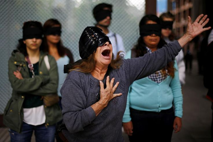 A demonstrator reacts during a rally in support of the 43 missing trainee teachers, from the Ayotzinapa teachers' training college in the Mexican state of Guerrero, near a gathering of members from the Alianza del Pacifico (Pacific Alliance) and MERCOSUR trade bloc in Santiago, Chile November 24, 2014.