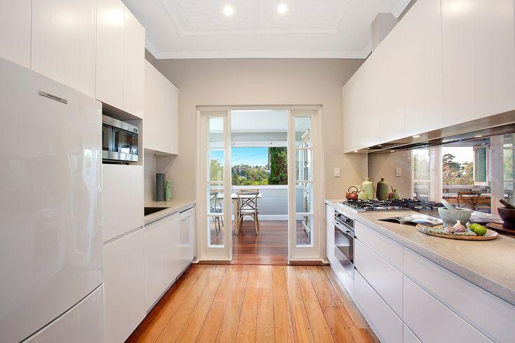 Caesarstone gas kitchen, wide oven, storage, mirrored splashback, timber flooring, downlights, styling, Pilcher Residential