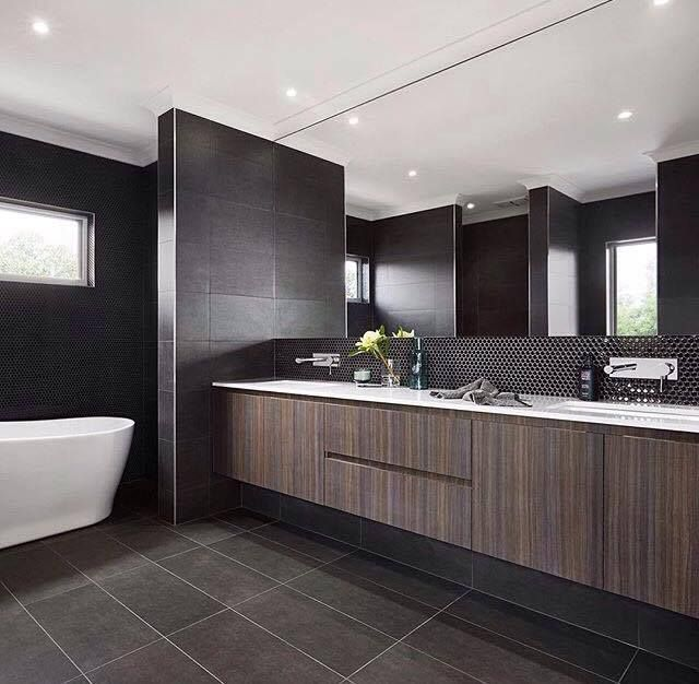 Black Penny Rounds making a statement under the mirror and behind the freestanding bath in @cartergrangehomes Essendon 41 display. @cartergrange  #tilestyle #tilespo