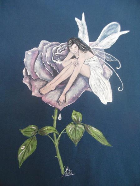 Hada sobre flor pintada a mano sobre camiseta.