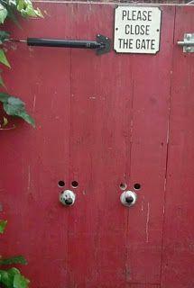 Foto de um portão de tábuas verticais pintadas em vermelho. Ao centro, abaixo, dois focinhos de cachorro, lado a lado,  encaixados, cada um em um buraco redondo. Acima de cada focinho, dois buracos menores redondos, por onde mal enxerga-se o brilho de pares de olhos mirando. No topo, entre as engrenagens de ferro do puxador e da tranca, uma placa quadrada em fundo branco, onde em letras maiúsculas pretas lê-se: Please, close the gate.