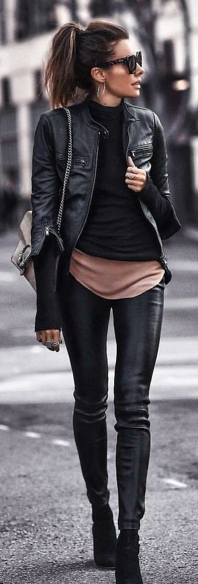 #spring #outfits woman in black leather zip-up jacket, black leggings, and pair of black suede boots holding grey leather chain crossbody bag. Pic by @ohmiloveit