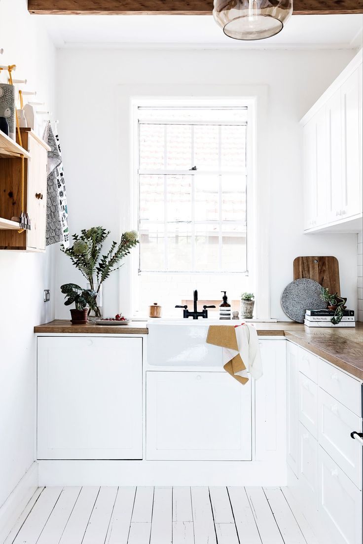 A bright little kitchen corner. I love the natural wood shelves and the plants! A clean and airy space.