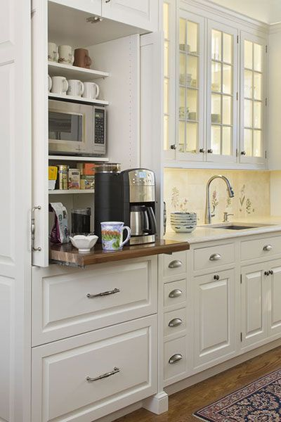 a coffee center located on a counter-height pullout shelf and a microwave on a shelf above.