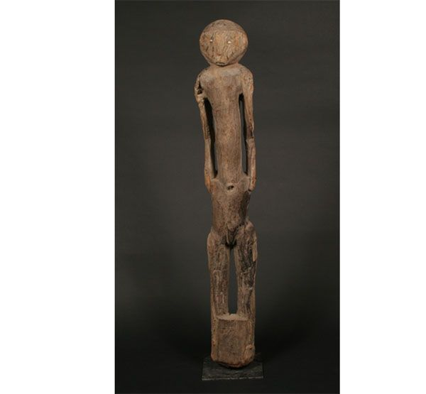 "A Tall Floor Standing Bongo memorial figure;Sudan; 4'8"". The large eroded figure made from African mahogany, with elongated body and small rounded head with inset aluminum eyes. Areas of burning, consistent with Bongo cultural traditions of farming that cause brush-fires that often burn the surfaces of the older figures in the field. Fine old surface. Rare and powerful.   Provenance: A private NY collection. H. 56 1/2"""