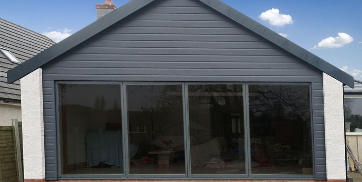 Anthracite Grey external cladding on a new home extension, with white rendered walls. Installation uses PVC Fortex cladding and Freefoam fascia boards.