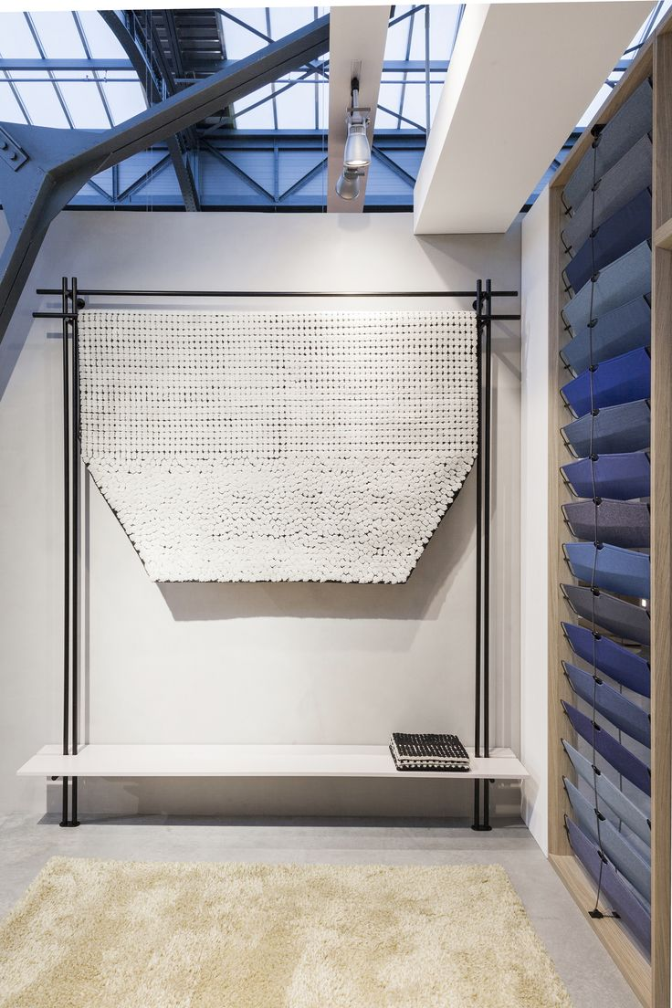 Danish-Italian design duo GamFratesi has skilfully reimagined Kvadrat's stand at Design Post Cologne, featuring a minimalistic wooden framework with rows of textile-covered panels in shades of blue