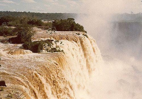 Salto de Sete Quedas, em Guaíra, estado do Paraná, Brasil. Imagem de Dezembro de 1978. Apesar do nome, eram constituídas por 19 cachoeiras principais, sendo agrupadas em sete grupos de quedas. Recordistas mundiais em volume d'água, as Sete Quedas eram o principal atrativo turístico de Guaíra. Estas quedas foram submersas para a formação do Lago da Usina Hidrelétrica de Itaipu, em outubro de 1982.  Fotografia: Mario Cesar Mendonça Gomes no Flickr.