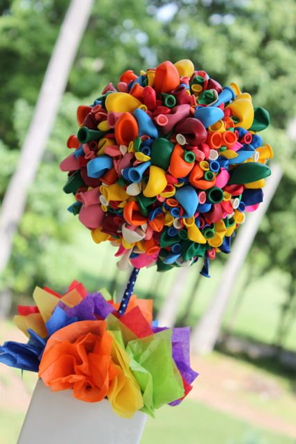 Balloon centerpieces.Balloons are glued to styrofoam. Ribbon is wrapped around stick. Tissue paper is stuffed inside container. The container possibly held icing. Add rocks to the bottom for weight before filling container.