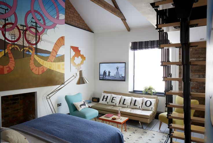Spacious #room with #eclectic #décor and original canvases by local #artist Mat McIvor. This #bedroom features a high vaulted ceiling, original #floorboards, #double #bed and ensuite shower room. A compact mezzanine has a further small single and double bed for little ones. #interiors #interior #design #cushions