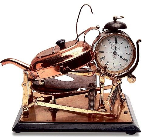 CLOCKWORK TEASMADE   Patented in Birmingham in 1902, this brass and copper tea maker was the first Teasmade. The alarm clock triggered a switch and a match was then struck against moving sandpaper, lighting the spirit stove under the kettle. Once the water boiled, the steam pressure lifted a hinged flap and the kettle would tilt, filling the teapot beneath. Finally, a plate would swing over the stove, extinguishing its flames.