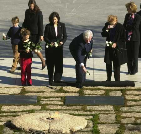 Sen. Edward Kennedy, lays a flower on the grave of his brother President John F. Kennedy, Tuesday, November 20, as family members Pat Kennedy Lawford, Sen. Kennedy's wife Victoria Kennedy, to his right and Kerry Kennedy Cuomo, far right.