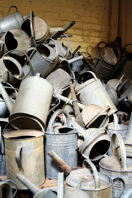 Pile of watering cans - this is a bit sad - they would be perfect for re-loving ie. painting and planting out!