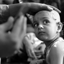 Its a moment of a little child while having his mundan having unwanted hair cut