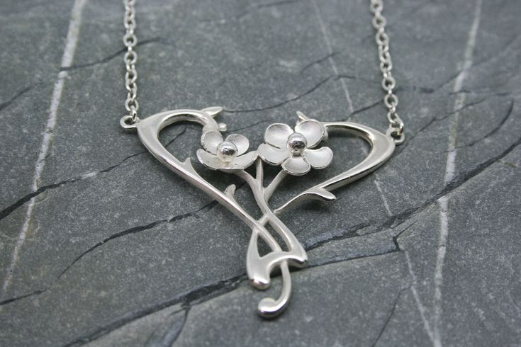 A sterling silver Art Nouveau styled pendant featuring three flowers with silver beads. The pendant was created in our own workshop in St. Ives Cornwall and is 2 inches wide and is supplied with a 16 inch trace chain.  #artnouveau #flower #necklace #pendant #silver #jewellery #cornwall #uk #gb #westcountry #devon #england #silversmith #pretty #jeweller #jewellers #handmadejewellery #handmade
