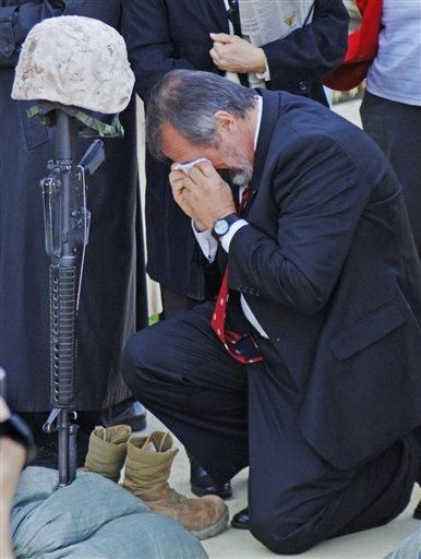 Stephen Reed of Columbus, kneels at his son's helmet, rifle and boots, following a memorial service for members of Lima Company, 3rd Battalion, 25th Marine Regiment, at the Navy and Marine Corps Reserve Center at Rickenbacker Base, Saturday, Nov. 12, 2005, in Columbus, Ohio. Reed's son, Lance Cpl. Aaron Reed was one of the soldiers killed in Iraq. (AP Photo/Mark Hall)