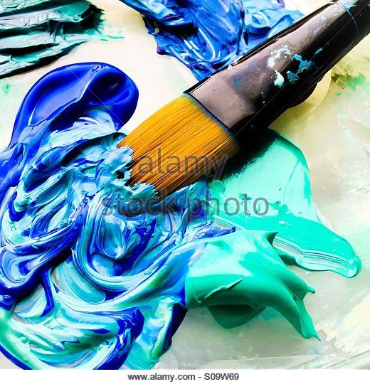 Paintbrush in blue and turquoise paint. - Stock Image