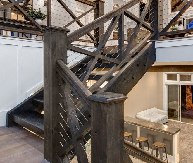 Leading to the basement, the main staircase features crossed wood balusters and cable railing. Timber Frame Home with Farmhouse-Inspired Interiors