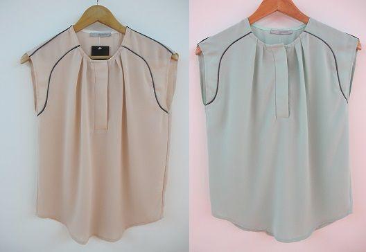 Top 1  Blusa sin mangas. Detalle de ribete en contraste en hombros. Abertura con tres botones en parte delantera.