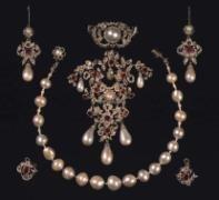 Garniture af perler, rubiner og diamanter med halskæde, broche og ørenringe. Udført 1840 af C.M. Weisshaupt. Perlekæden har tilhørt Christian 5.s dronning Charlotte Amalie.