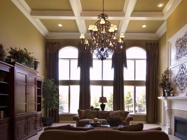 The beautiful iron and crystal chandelier adds an element of interest in this stunning traditional great room. The use of long paneled draperies, along with the medallion hardware accentuates the dramatic circle top wall of windows.