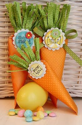 "Designer Tips: -Carrots can be made to any size, I created mine a bit taller and thinner to resemble carrots. For the large carrots, I cut my paper to 5""w x 6""h and for the smaller carrot, I cut it to 4""w x 5""h. -I crimped the Double Dot Avocado Cardstock and cut a fringe to create the green carrot tops. -To hang the carrot containers, punch a hole near the bottom of the green carrot top and insert the fold of the ribbon to create a loop in the back, then tie a bow in the front."