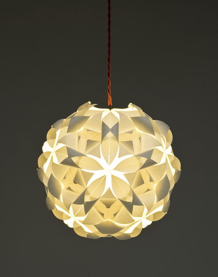 paper lamp shade. i like the design of this lamp as each cut in the pattern allows a different shade of light to come through and reflect patterns onto the wall (if it was dark).