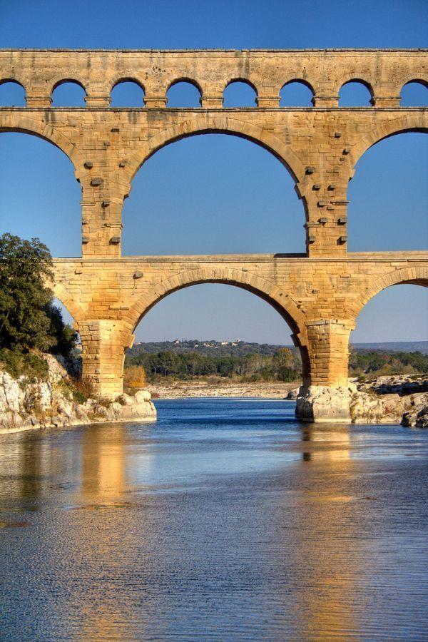 Pont du Gard, is an ancient Roman aqueduct bridge that crosses the Gardon River in France