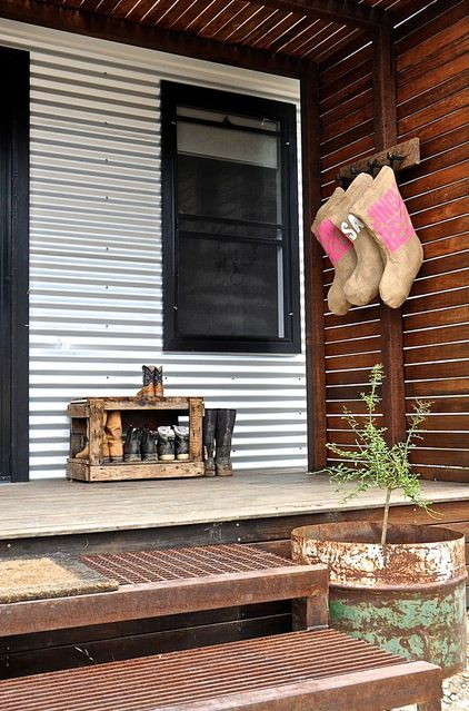 The porch steps are made from a repurposed cattle grid, while potted plants hunker down in 44-gallon fuel drums cut in half.