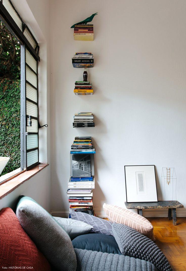 Almofadas usadas como sofá e prateleira invisível decoram essa sala de estar.
