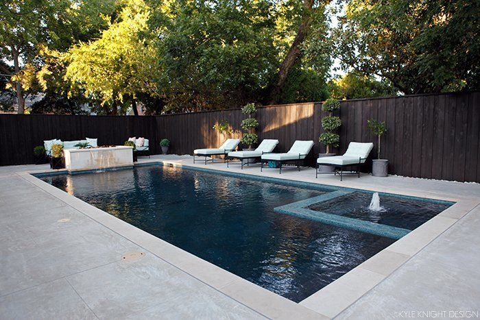 "The new pool has Lueders limestone coping, a concrete pool deck with a light acid wash, onyx quartz plaster, and the waterline tile is Noble Cobblestones 1"" in the Ocean color. Gas firepit doubles as a waterfall. Inset hot tub."