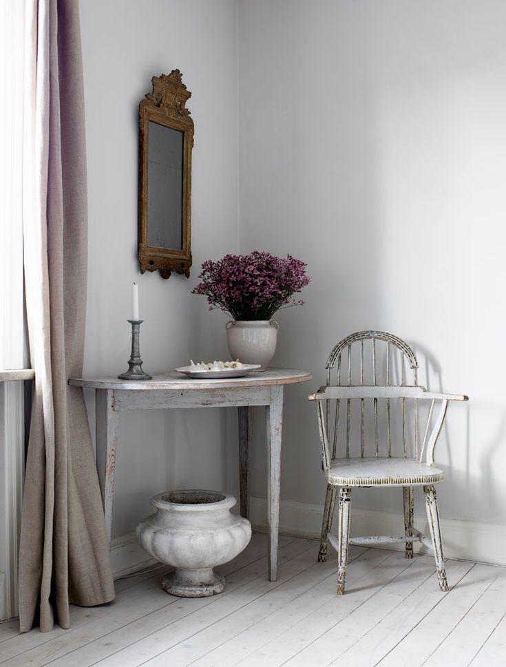 """Två sengustavianska halvmånebord står på varsin sida om fönstret i matrummet och skapar symmetri. Stolen från första hälften av 1800-talet kommer från Medevi brunn i Östergötland, Magnus har flera """"för att de är så sköna och vackra, nästan skulpturala"""". 1800-talsurnan är fransk och den hallstämplade gustavianska spegeln är helt i original."""