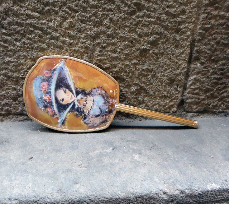 Sweety vanity brass hand mirror with golden metal frame. The back of the brush and mirror one can see the portrait of a little girl. The set is in excellent vintage condition. Measures: L29 x W12 cms