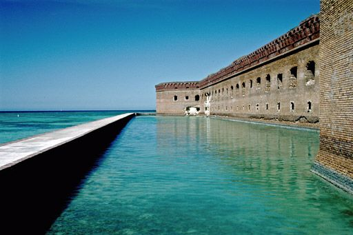 Dry Tortugas National Park. The Dry Tortugas on the west end of the Florida Keys are the site of Fort Jefferson, the largest masonry structure in the Western Hemisphere. With most of the park being water, it is the home of coral reefs and shipwrecks and is only accessible by plane or boat