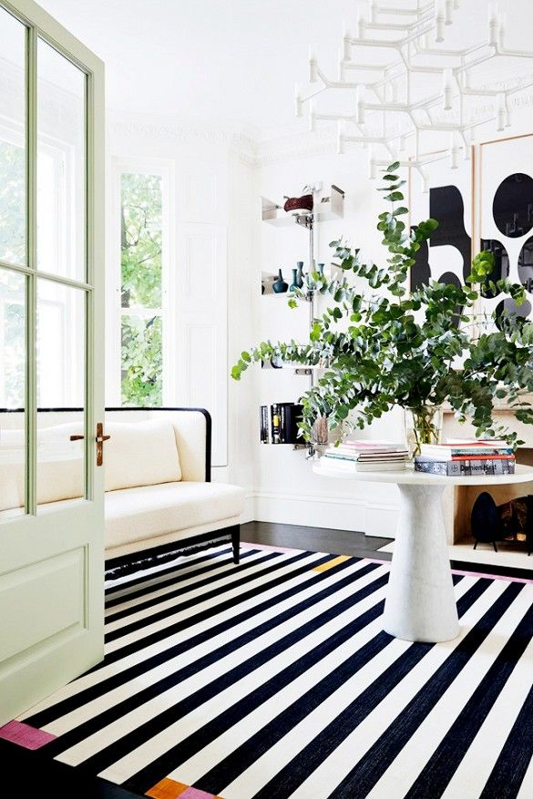 Mint door with stripe rug and abstract art