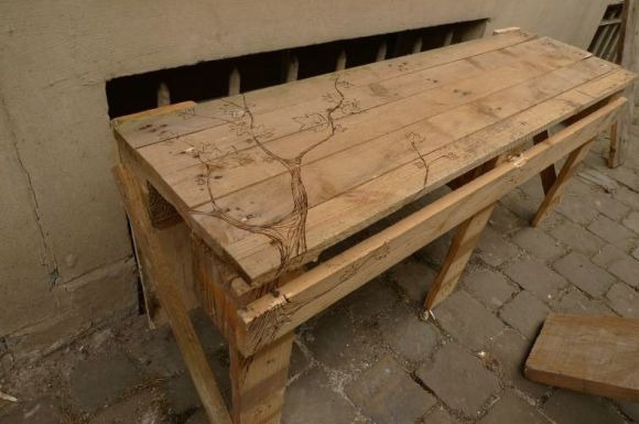 One-pallet wood DIY park bench, artfully decorated with a wood-burned tree design.