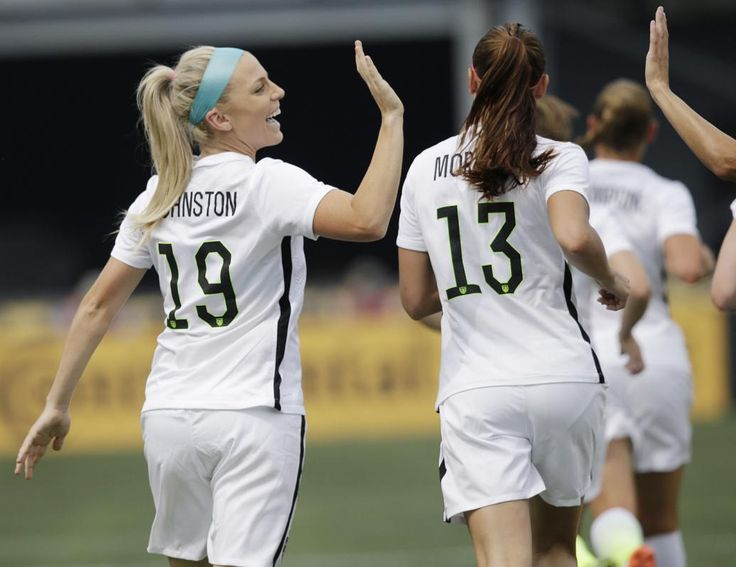 United States' Julie Johnston, left, celebrates a goal with teammates during the U.S. Women's World Cup soccer victory tour, Sunday, Sept. 20, 2015, in Birmingham, Ala. (AP Photo/Brynn Anderson)