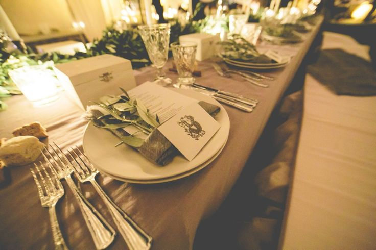 The wedding table is decorated with olive brunches, linen napkins and sparkling candles!