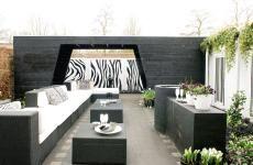 Gezien op TV bij Eigen Huis & Tuin? Dezelfde achtertuin, in drie verschillende stijlen en sferen. Met als enige beperking voor de inrichting de bestaande berging. Die mocht natuurlijk wel worden aangepakt. Lengte van de tuin is: 10,75 m en de breedte is: 8,80 m.  Vergrijsde kleuren, robuuste elementen, natuurlijke uitstraling. Denk aan Reykjavik en ervaar de minimalistische trendy stijl. Toeval wilde dat het bij het fotograferen van deze tuin hagelde.