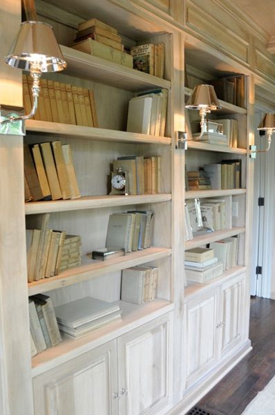 Pretty bookshelves with lower cabinets and sconces with polished nickel shades.