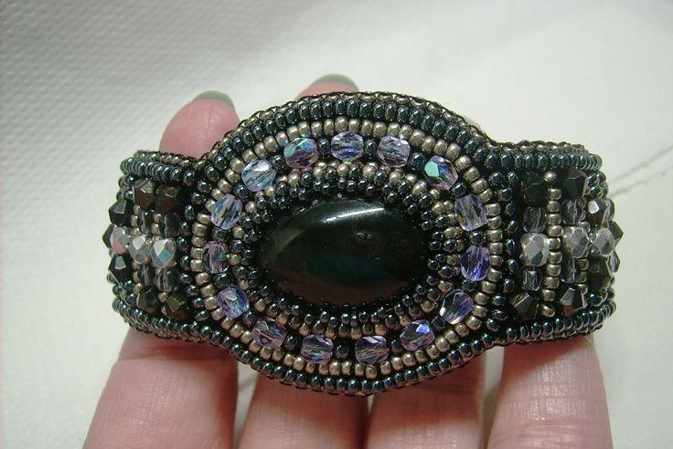 K-601. Fekete színű, Achát köves, szürke, lila és ezüst színű, üveg gyöngyös, gyöngy-hímzett, gombbal kapcsolható karkötő. 3900.-Ft