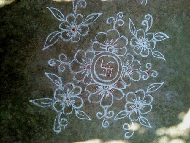 Floral design Rangoli with four flowers in four directions.
