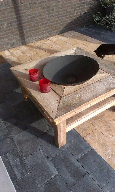 Vuurschaal in steigerhouten tafel. Op het onderste blad kun je je voeten s,avonds lekker warmen  aan het vuur.