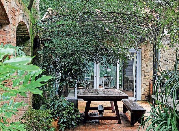 Jardim que parece mata preservadaAo lado da cozinha, o espaço é usado para tomar café e almoçar ao ar livre. Tutorada no pergolado de ferro, trepadeira jasmim-dospoetas. Em primeiro plano, do lado esq., leia-verde. À dir., íris-azul (Foto: Raphael Briest/Divulgação)