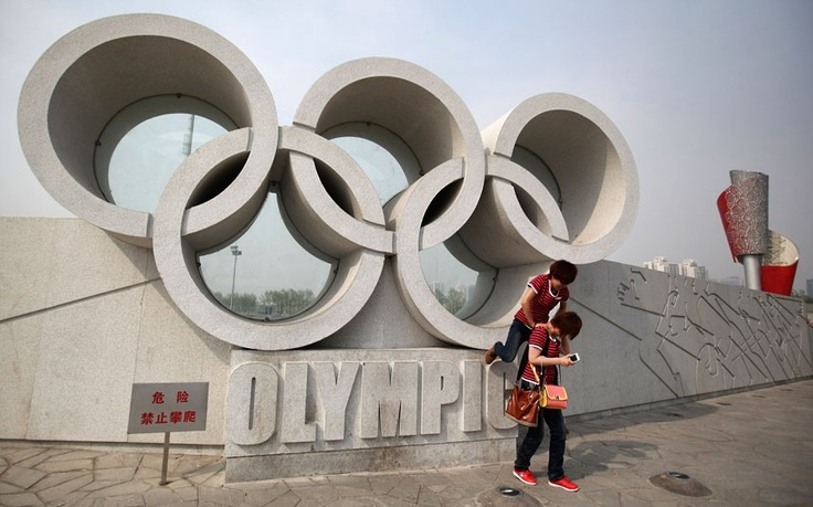 London 2012 Olympics: 100 days to go to the Games - Two women play near an Olympic rings sculpture and the torch of the Beijing Olympic Games before a rehearsal for a ceremony to mark the 100-day countdown to London 2012 Picture: Feng Li/Getty Images